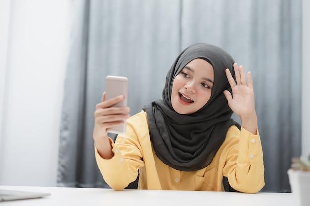 Mulher muçulmana fazendo videochamada usando smartphone