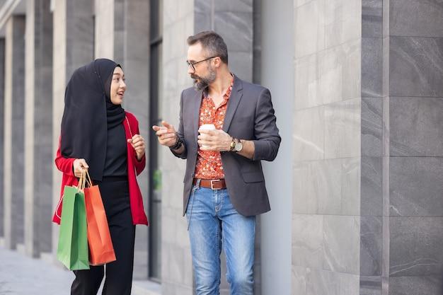 Mulher muçulmana feliz com sacolas de compras e homem com café para viagem