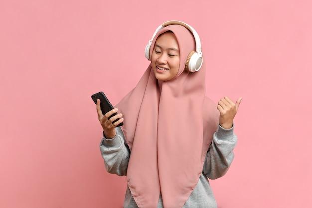 Mulher muçulmana feliz e cheia de energia dança alegremente, gosta de música favorita, usa fones de ouvido estéreo, isolado em um fundo rosa e expressa humor positivo