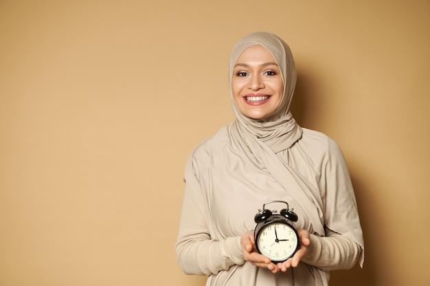 Mulher muçulmana feliz em hijab segura um despertador nas mãos e sorri com um sorriso largo, olhando para a frente em uma superfície bege com espaço de cópia