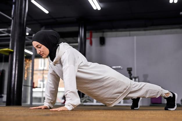 Mulher muçulmana forte fazendo um conjunto de flexões em uma academia, mulher atleta esportiva no hijab concentrada no treino.