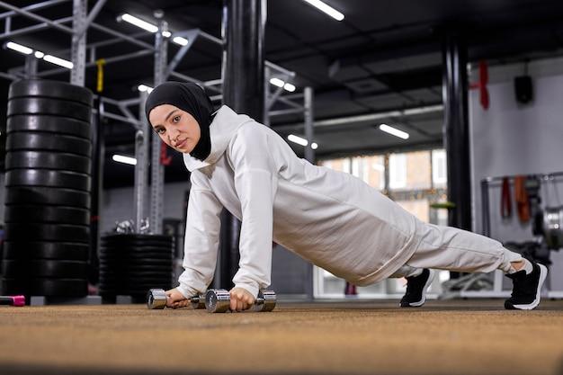Mulher muçulmana forte fazendo uma série de flexões em uma academia, mulher atleta esportiva em hijab concentrada no treino, usando halteres, ela olha para a câmera com confiança
