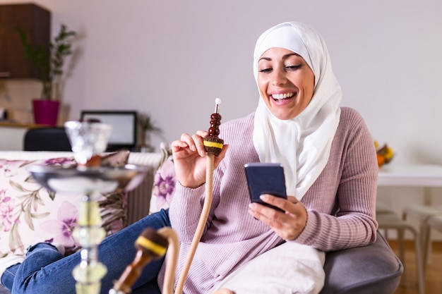 Mulher muçulmana fumar shisha em casa e mensagens de texto com seus amigos. menina árabe fumar cachimbo de água