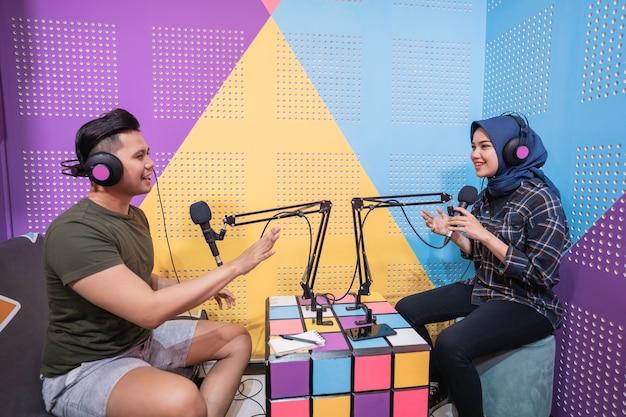 Mulher muçulmana gravando podcast com um homem no estúdio