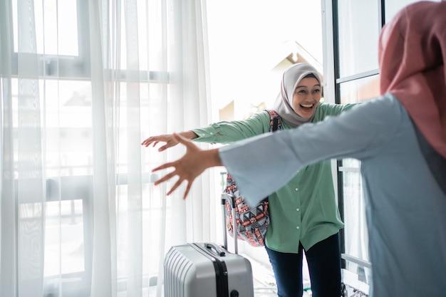Mulher muçulmana hijab feliz encontra sua irmã