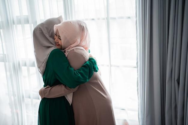 Mulher muçulmana hijab felizmente conhece e abraça sua irmã