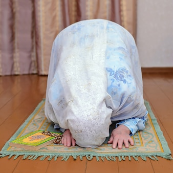 Mulher muçulmana idosa com um vestido azul brilhante e um lenço branco reza no tapete de oração verde