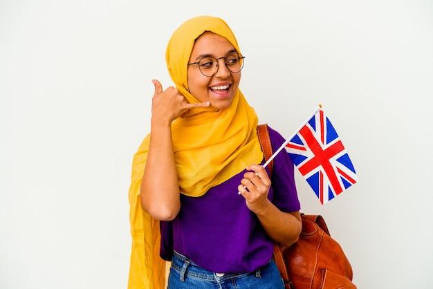 Mulher muçulmana jovem estudante isolada no fundo branco, mostrando um gesto de chamada de telefone móvel com os dedos.