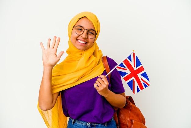 Mulher muçulmana jovem estudante isolada no fundo branco, sorrindo alegre mostrando o número cinco com os dedos.