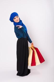 Mulher muçulmana jovem feliz com sacola de compras em fundo branco.