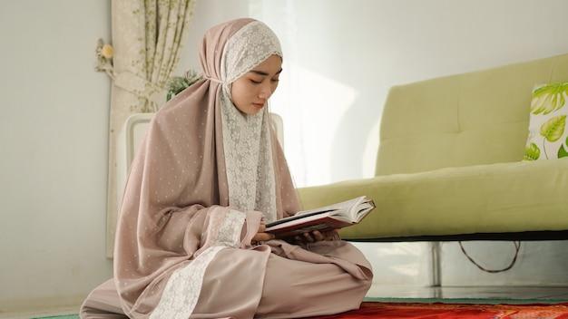 Mulher muçulmana lendo o alcorão seriamente em casa