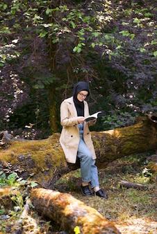 Mulher muçulmana lendo um livro no parque durante seu tempo livre.