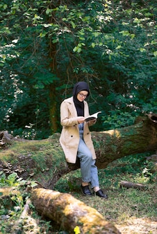 Mulher muçulmana lendo um livro no parque nas horas vagas