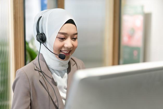 Mulher muçulmana linda sorridente trabalhando no atendimento ao cliente usando fone de ouvido e conversando com o cliente no escritório