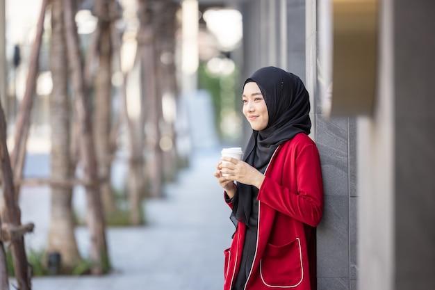 Mulher muçulmana moderna atravessando a rua com um café para viagem