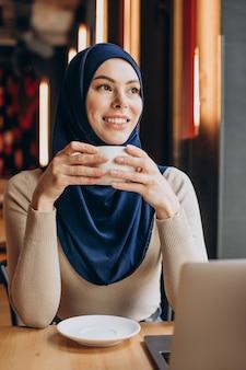 Mulher muçulmana moderna bebendo chá e trabalhando no computador em um café