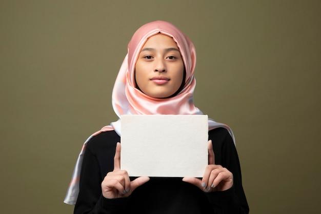 Mulher muçulmana mostrando um cartão em branco