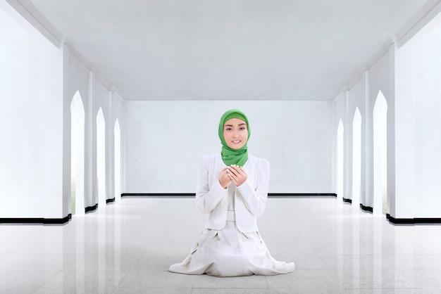 Mulher muçulmana muito asiática rezando a deus