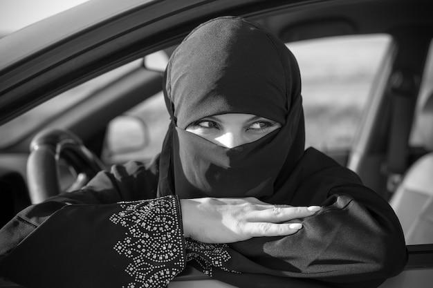 Mulher muçulmana na fila de espera no engarrafamento. preto e branco