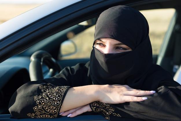Mulher muçulmana na fila de espera no engarrafamento.