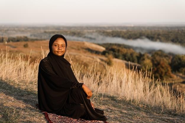 Mulher muçulmana negra com manto sentado no tapete. solat tradicional orando a deus.