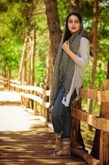 Mulher muçulmana no xale de seda cinza no parque