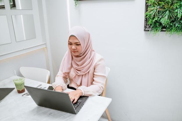 Mulher muçulmana nova que usa o portátil preto. mulher de negócios asiática nova que senta-se na cafetaria e que trabalha no portátil.