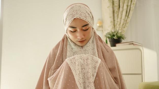 Mulher muçulmana orando e rezando usando uma mukenah