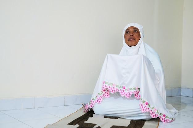 Mulher muçulmana orando em sua casa