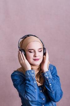 Mulher muçulmana ouvindo música em fones de ouvido