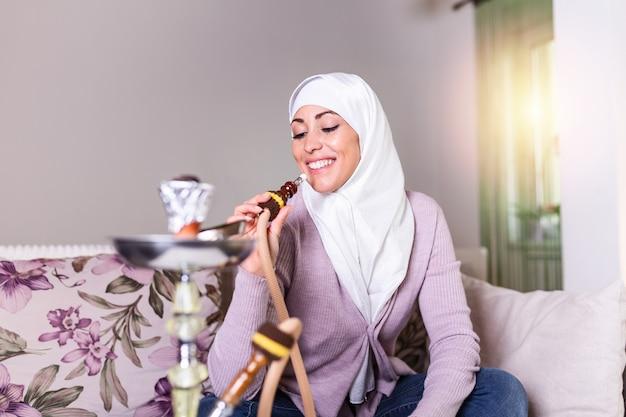 Mulher muçulmana que fuma shisha em casa. menina árabe fumar cachimbo de água