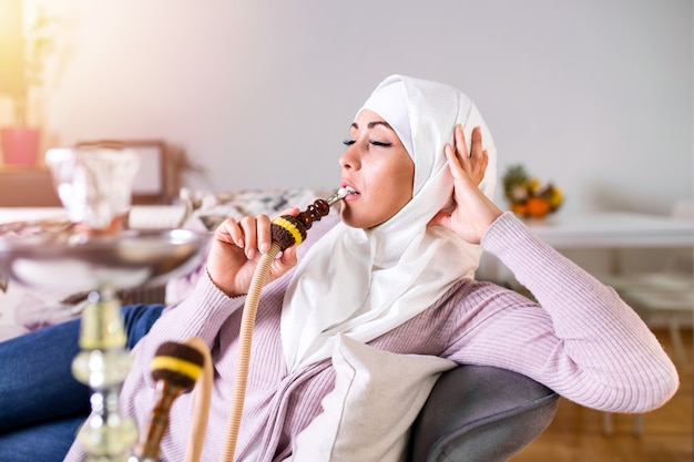 Mulher muçulmana que fuma shisha em casa que aprecia ao fumar nargile.