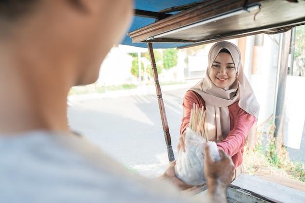 Mulher muçulmana recebendo seu pedido de comida de frango satay