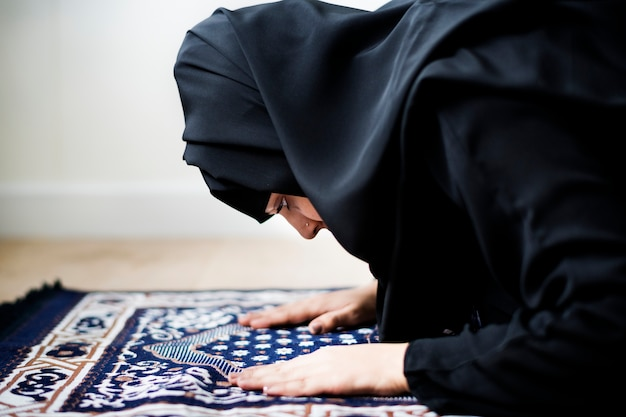 Mulher muçulmana rezando em postura de sujud