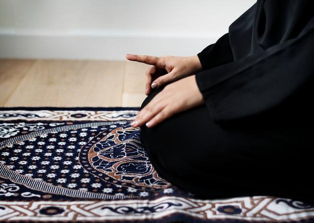 Mulher muçulmana rezando na postura de tashahhud