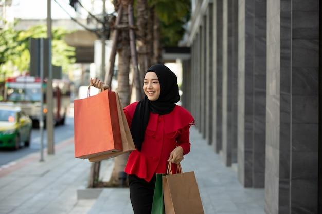 Mulher muçulmana segurando sacola de compras
