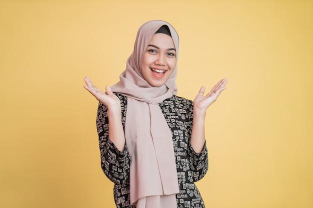 Mulher muçulmana sorridente com véu levantando a mão no queixo e sorrindo feliz
