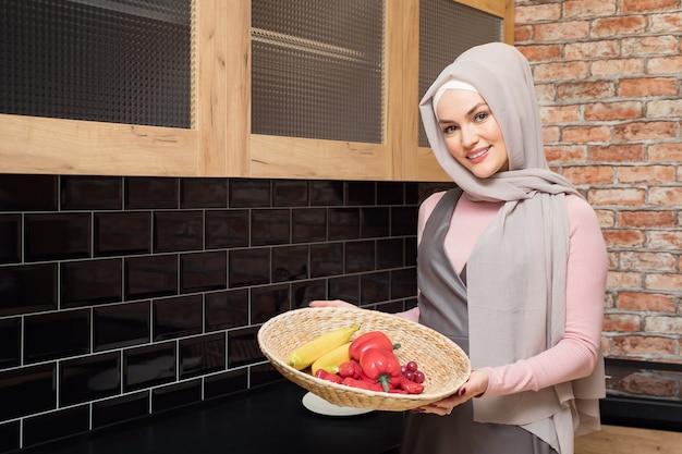 Mulher muçulmana sorridente em hijab segurando uma tigela de vegetais copiar o espaço