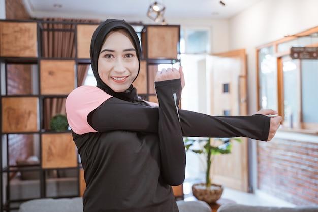 Mulher muçulmana sorridente em roupas esportivas estende-se com uma mão segurando a outra quando uma delas é puxada para o lado enquanto faz atividades na casa