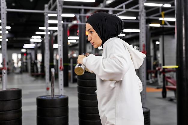 Mulher muçulmana treinando na academia usando halteres, fazendo exercícios intensos sozinhas em uma academia moderna, usando um hijab esportivo branco