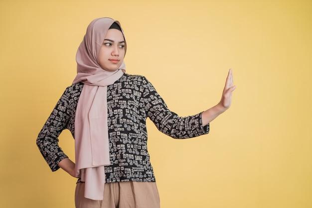 Mulher muçulmana usando hijab com gesto de mão rejeitando oferta com espaço