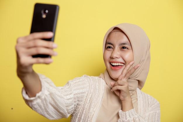 Mulher muçulmana usando hijab feliz selfie com telefone isolado em fundo amarelo