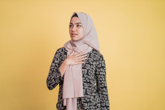Mulher muçulmana usando hijab segurando o peito com expressão calma