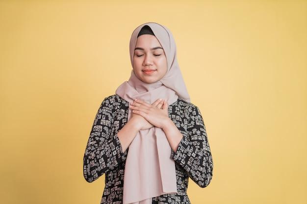 Mulher muçulmana usando hijab segurando o peito e os olhos fechados com expressão paciente