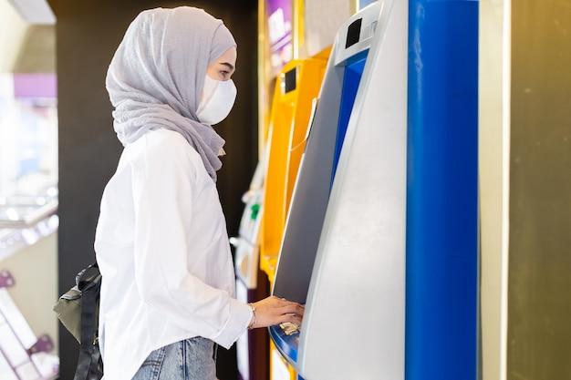 Mulher muçulmana usando máscara médica para evitar vírus de infecção usando o caixa eletrônico para sacar dinheiro nas ruas da cidade.