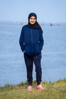 Mulher muçulmana vestindo roupas escuras e hijab cobre seu cabelo em pé