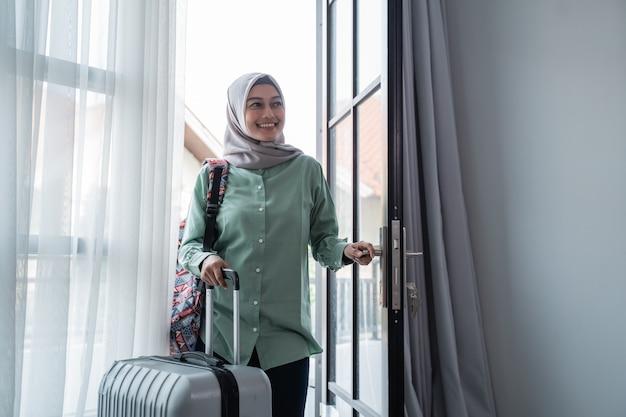 Mulher muçulmana viajante abriu a porta de entrada com sua bolsa e mala