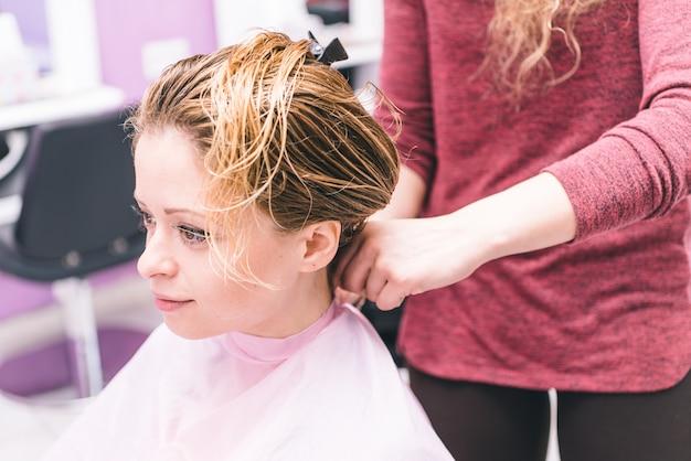 Mulher mudando o novo estilo de cabelo no salão