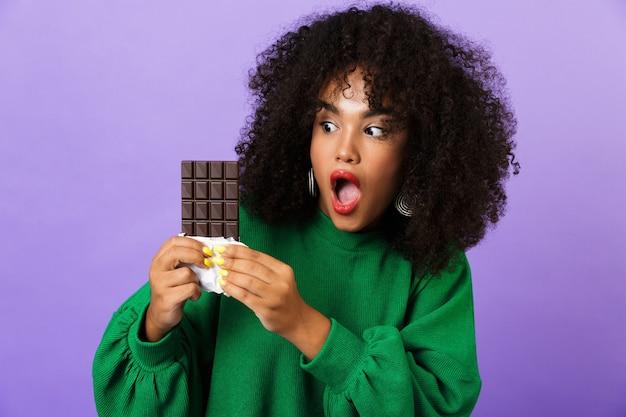 Mulher muito africana animada isolada sobre o espaço violeta come chocolate.