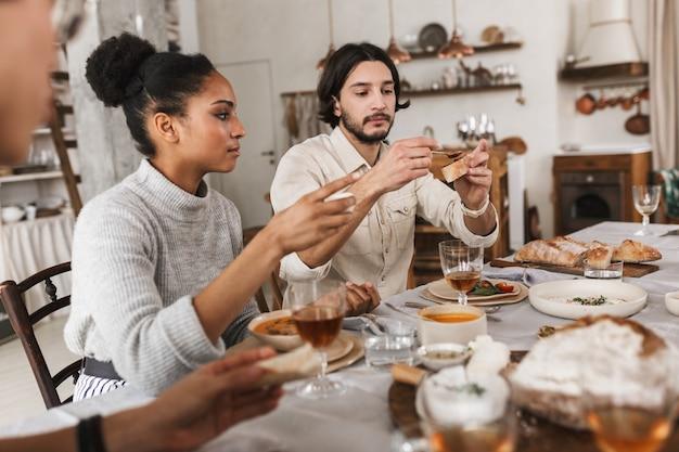 Mulher muito afro-americana e um homem bonito com barba sentado à mesa comendo pão sonhadoramente